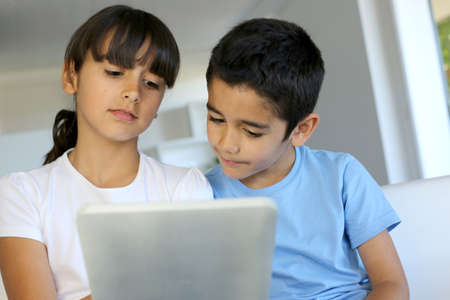 latin kids: Children playing with electronic tablet at home