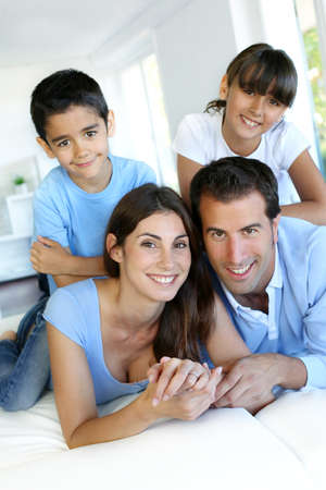 latin family: Portrait of happy family laying down bed
