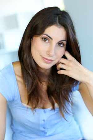 Portrait of attractive brunette woman with hand on chin