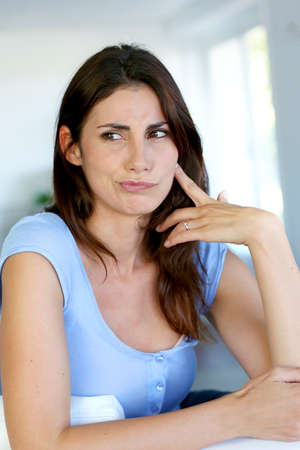 sceptical: Brunette girl with questioning look on her fave Stock Photo