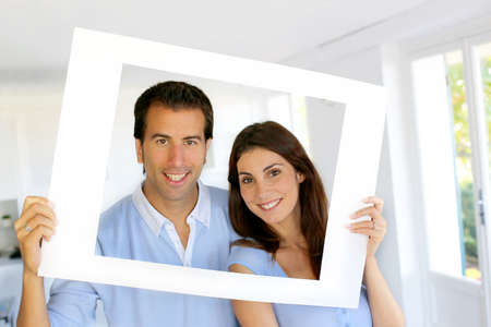looking through frame: Closeup of cheerful couple looking through frame Stock Photo