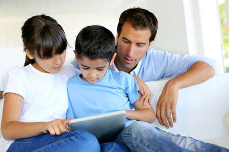 Father controlling children while playing on tablet Stock Photo - 14663576