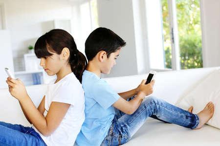 Bambini che giocano in casa con gli smartphone Archivio Fotografico