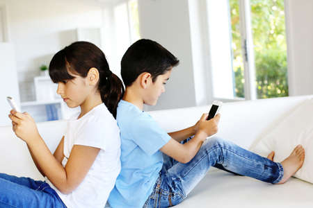 latin kids: Kids playing at home with smartphones