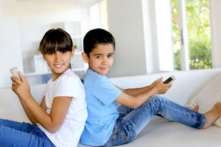 Kids playing at home with smartphones photo