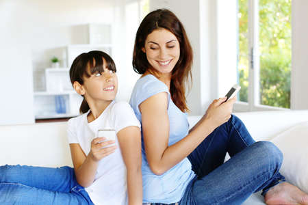 latin kids: Mother and daughter using mobile phone at home
