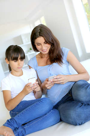 Mother and daughter using mobile phone at home photo