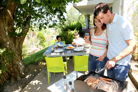 Family cooking meat on barbecue grill photo
