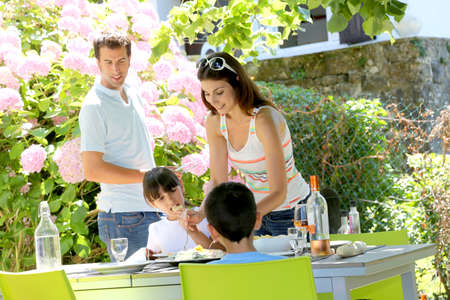 Mother serving lunch to kids in home garden Stock Photo - 14663657
