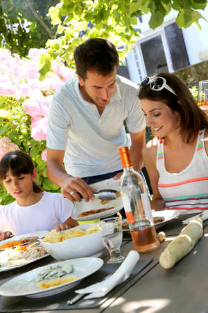 Father serving grilled meat to family photo