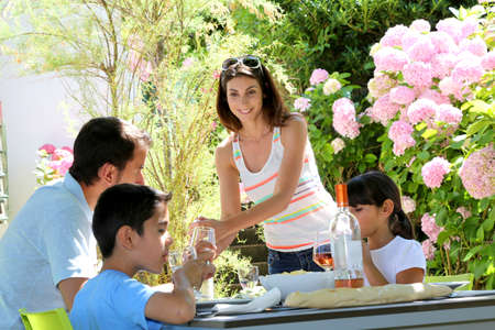 Woman serving water to family having lunch photo