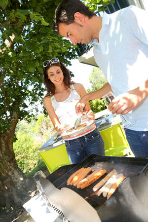 Couple cooking meat on barbecue grill photo