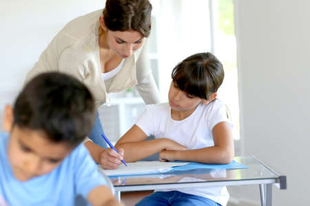 10 year old: Teacher helping young girl in class with lesson Stock Photo