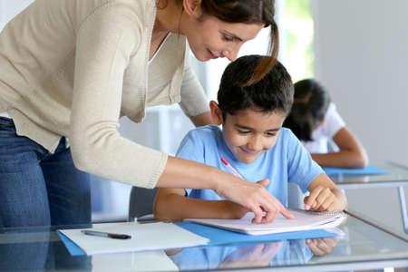ni�os ayudando: Profesor ayudando muchacho joven con la escritura de la lecci�n Foto de archivo