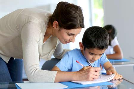 Niños ayudando: Profesor ayudando muchacho joven con la escritura de la lección Foto de archivo