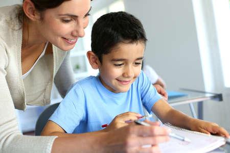 profesor alumno: Profesor ayudando muchacho joven con la escritura de la lecci�n Foto de archivo