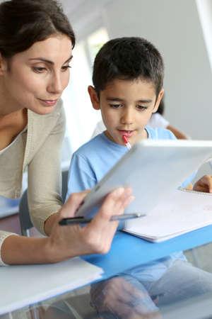 maestra ense�ando: Profesor y colegial que usa la tableta electr�nica en la clase