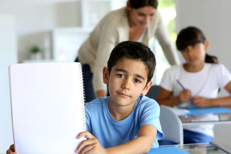 Portrait of cute little boy showing notebook towards camera photo