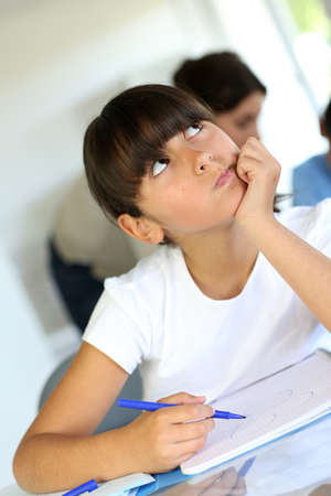 Closeup of schoolgirl in class with thoughtful look photo