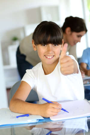 Closeup of little girl in class showing thumb up photo