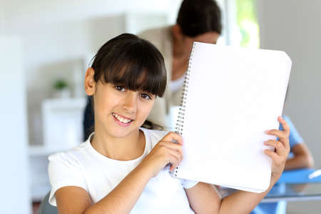 Closeup of beautiful school girl showing notebook page  photo