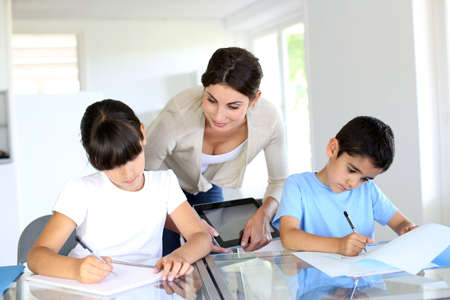 studing: Teacher and kids in classroom writing on notebook