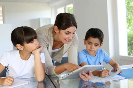 Woman teaching class to school children with digital tablet Stock Photo - 14663608