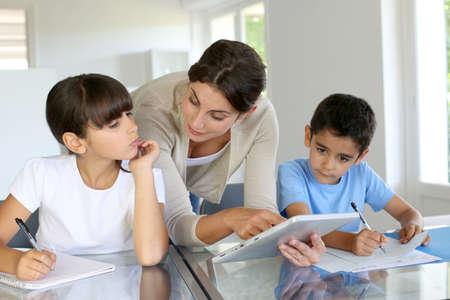 teacher teaching: Woman teaching class to school children with digital tablet