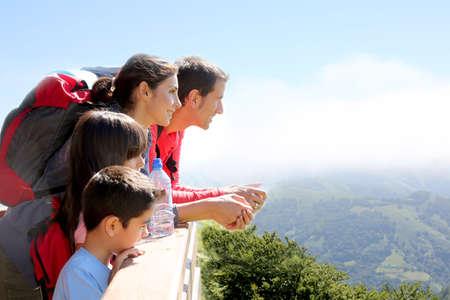 férias: Família em um dia caminhada na montanha olhando a vista Imagens
