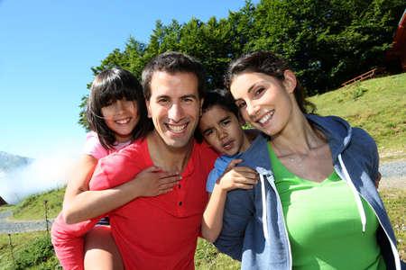 padres e hijos felices: Los padres y niños de pie en paisaje natural