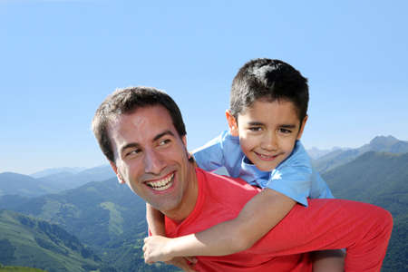 latin family: Portrait of father and son having fun in the mountain