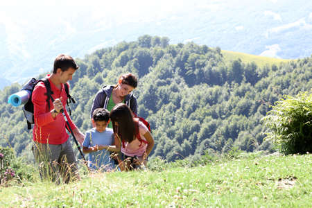 Family on a trekking day looking at wild flowers Stock Photo