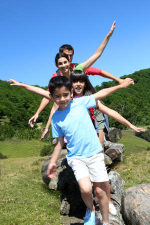 Family of four standing on rocks in the mountain photo