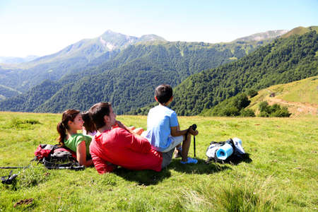 panoramic nature: Family laying down the grass enjoying mountain view Stock Photo