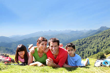 Portrait of happy family laying on the grass in mountain photo