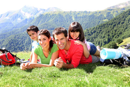 Portrait de famille heureuse couché sur l'herbe en montagne