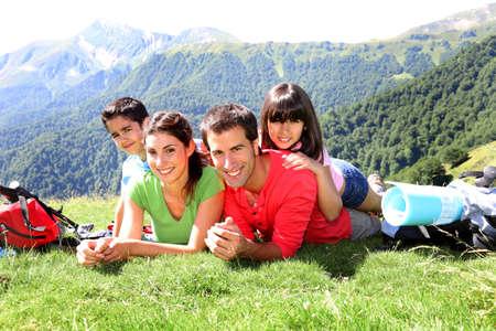 Retrato de familia feliz que pone en la hierba en la montaña