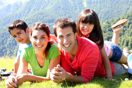 Portrait of happy family laying on the grass in mountain Stock Photo - 14663675