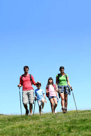 Family of four hiking in the mountain by sunny day photo