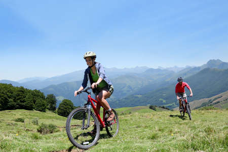 woman bike: Couple riding bicycles in the mountains
