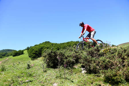 Man riding mountain bike in summertime photo