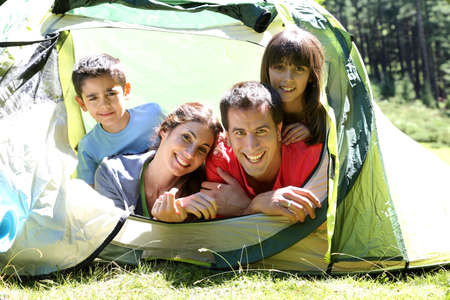 Portrait of family laying in camp tent photo