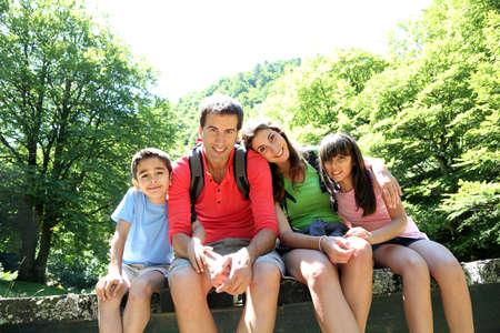 두서없는: 가족이 숲에서 다리에 앉아의 초상화 스톡 사진
