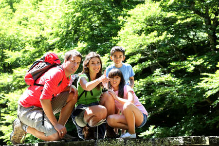 Family on a bridge in mountain observing nature photo