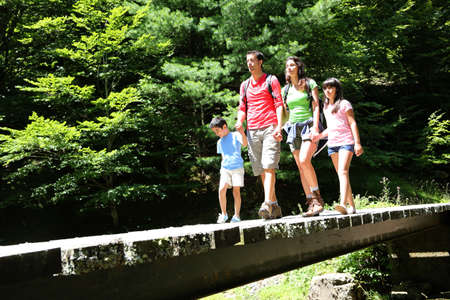 Family walking on a bridge in mountain forest photo