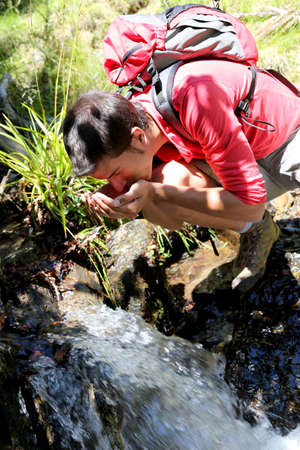 Man on a trekking day drinking water from river photo