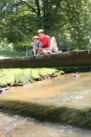 Father fishing with son on a bridge in the mountain Stock Photo - 14663715