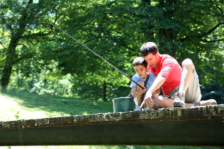 angler: Father fishing with son on a bridge in the mountain