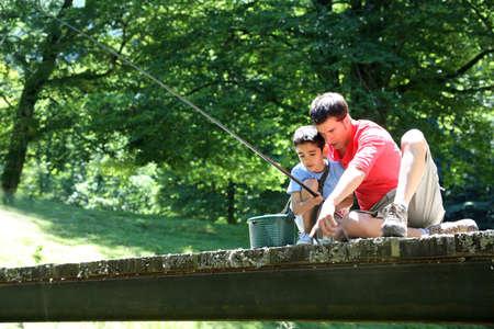 hombre pescando: Padre con el hijo de pesca en un puente en la monta�a Foto de archivo