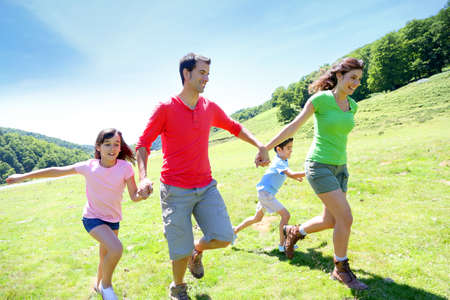 Happy family enjoying and running together in the mountains photo